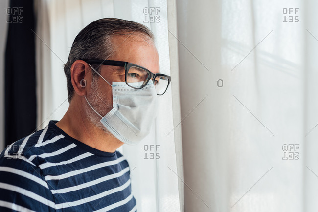 Side view of man wearing face medical mask standing on windows looking away during lockdown