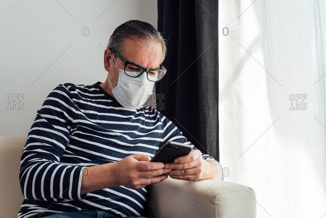 Focused male in glasses using on mobile phone and laptop while working at home because of quarantine