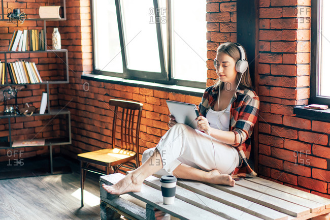 Young barefoot female student in headphones studying while watching tablet and sitting on wooden bench with crossed legs near disposable glass of coffee in loft style living room in sunlight