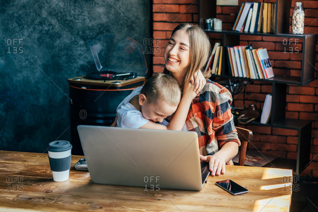 Adorable boy cuddling gently and kissing smiling woman with closed eyes sitting at table with netbook and disposable glass of coffee in loft style flat