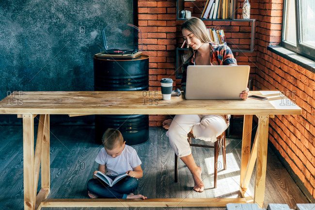Little child reading book while sitting with crossed legs under wooden table near barefoot woman with netbook and plastic glass of coffee in loft style living room