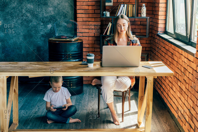 Little child browsing phone while sitting with crossed legs under wooden table near barefoot woman with netbook and plastic glass of coffee in loft style living room