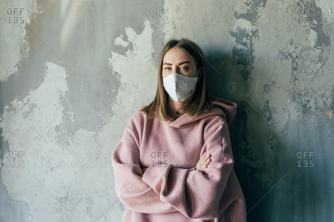 Unrecognizable discontent female in pullover and sterile mask standing with crossed arms near cement wall with shabby surface in flat and looking at camera during COVID 19 pandemic