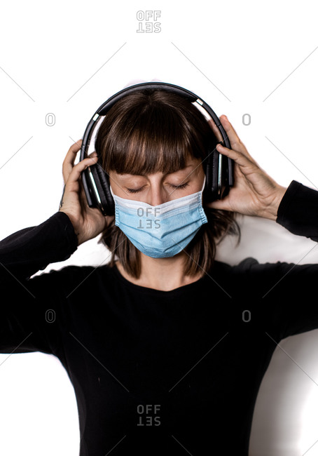 Young tattooed woman in medical mask with mobile phone enjoying music with closed eyes in headphones against white background