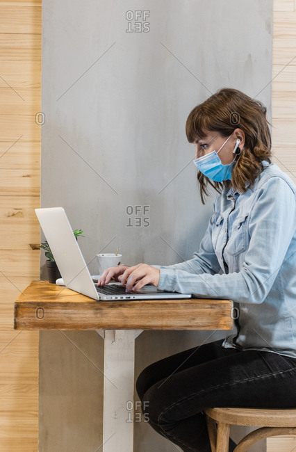 Side view of focused female freelancer in denim shirt and medical mask using earbuds and working remotely in cafe using laptop during coronavirus epidemic