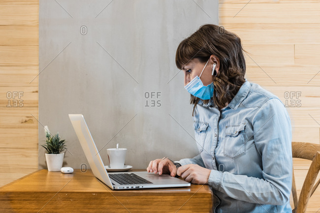 Focused female freelancer in denim shirt and medical mask using earbuds and working remotely in cafe using laptop during coronavirus epidemic