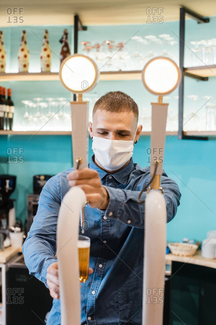 Positive young male bartender in protective mask and denim shirt pouring beer from tap while working in pub