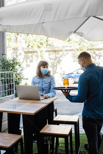 Waiter serving glass of fresh beer for woman in medical mask working remotely on laptop in outdoor cafe