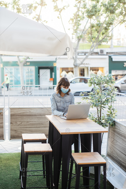 Woman in medical mask working remotely on laptop in outdoor cafe