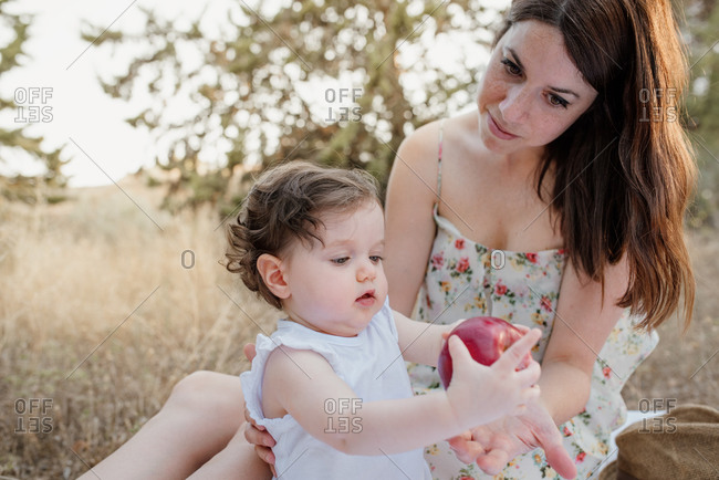 Young mom in floral sundress sharing ripe red apple with adorable little daughter in white sleeveless top while relaxing on withered glade in summer countryside