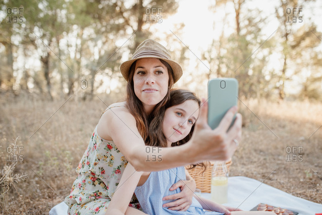 Young mother and daughter in sundresses taking selfie on smartphone while having picnic in quiet summer park on sunny day