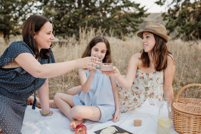 Parents and daughter together with youthful appearance all wearing summer dresses clinking glasses with refreshing lemonade while sitting on picnic blanket on quiet rural glade