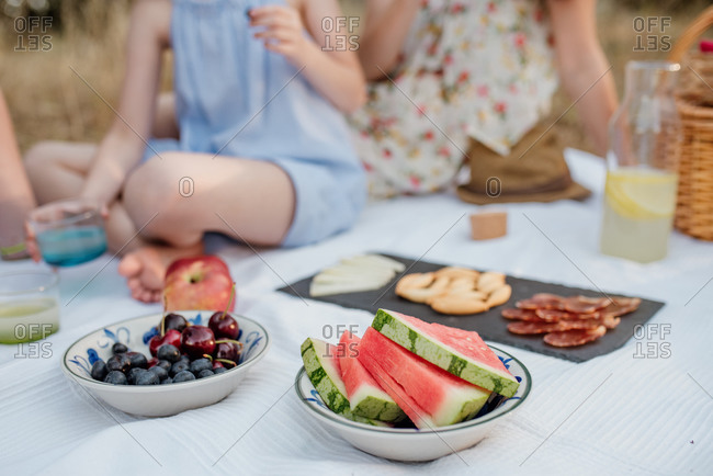 Crop anonymous people with board with prosciutto and seeds while sitting on white cloth with fruit and lemonade during summer picnic