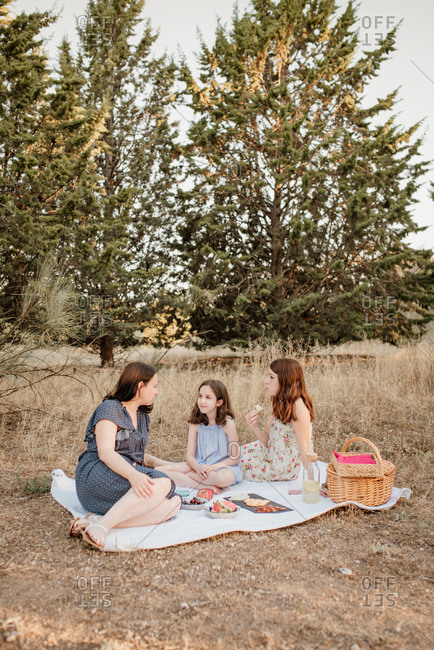 Parents and daughter together with youthful appearance all wearing summer dresses drinking refreshing lemonade while sitting on picnic blanket on quiet rural glade