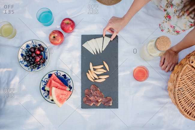 Top view of crop anonymous woman picking slice of parmesan from board with prosciutto and seeds while sitting on white cloth with fruit and lemonade during summer picnic