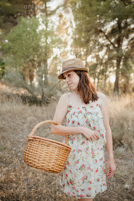 Charming woman in sundress and hat with wicker basket over arm standing on picnic blanket in back lit in summer park and looking away