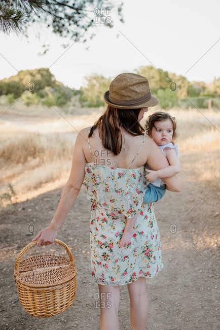 Back view of young mom in floral sundress carrying cute little daughter and picnic wicker basket on sunny day in countryside