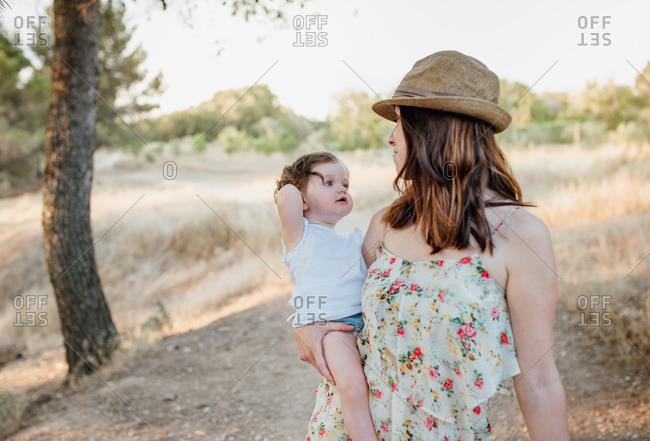 Young mom in floral sundress carrying cute little daughter on sunny day in countryside