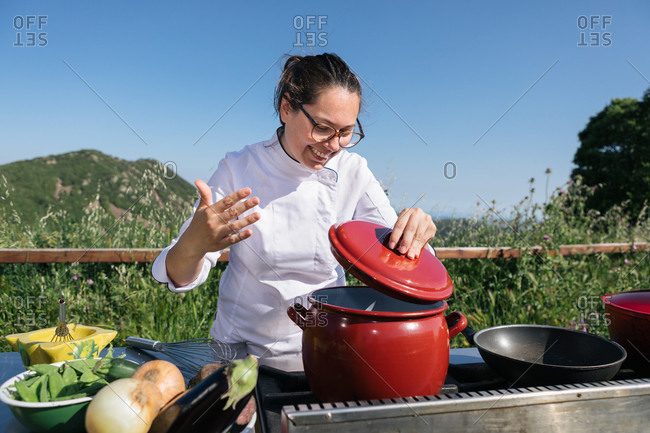 Crop concentrated male chef in tunic and apron preparing delicious dish in saucepan standing at table in outdoor kitchen against picturesque mountains