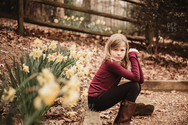 Girl sitting by a garden