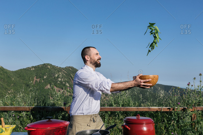 Side view of happy bearded cook smiling and tossing vegetables in bowl while preparing healthy lunch in nature near beautiful mountains