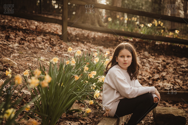 Young brunette girl sitting by a garden