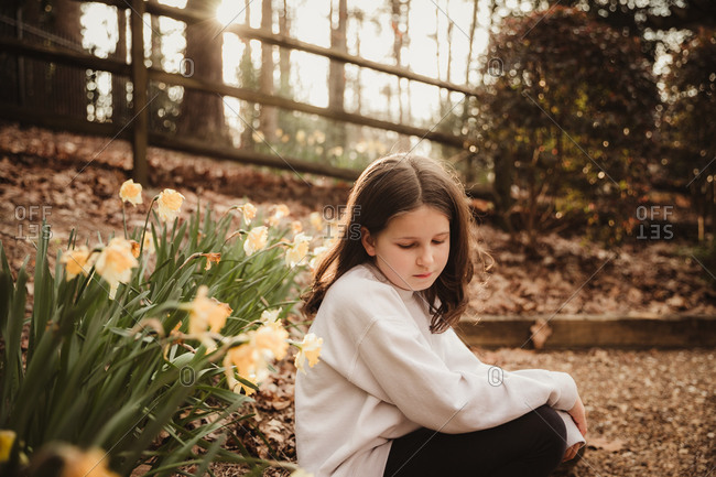 Girl sitting by a garden in springtime looking down