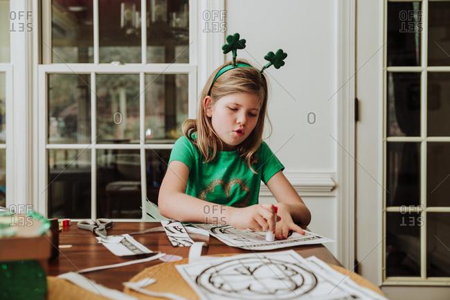 Girl wearing shamrock headband working on a Saint Patrick's day craft