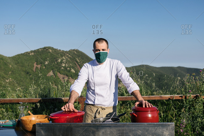 Unrecognizable male chef in uniform and medical mask standing near saucepans in outdoor kitchen and looking at camera