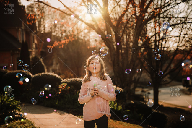 Girl blowing bubbles outside her home