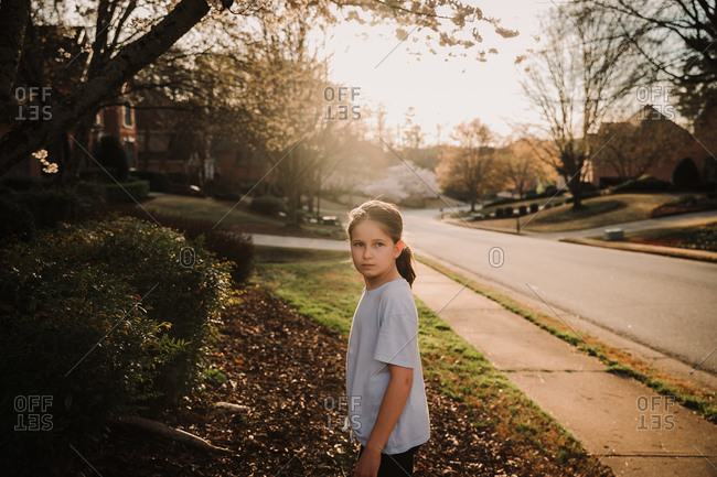 Portrait of a girl looking at something in the distance while standing in front of her home