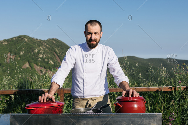 Male chef in uniform standing near saucepans in outdoor kitchen and looking at camera