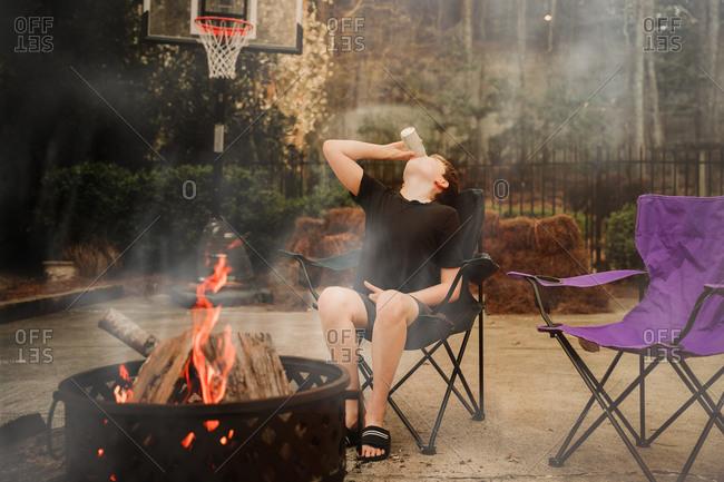 Boy drinking soda by a fire pit