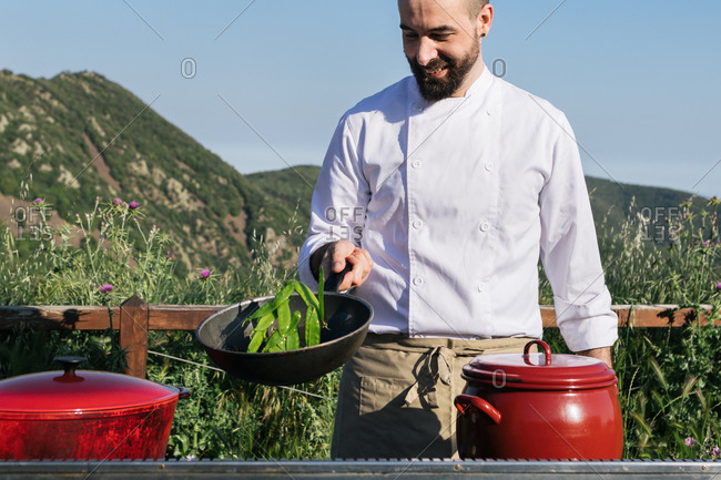 Happy bearded male cook in tunic spicing dish in pan while preparing delicious dish against blurred mountains during workshop in nature