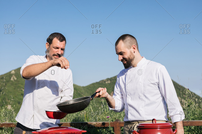 Low angle of happy bearded male cooks in tunics spicing dish in pan while preparing delicious dish against blurred mountains during workshop in nature