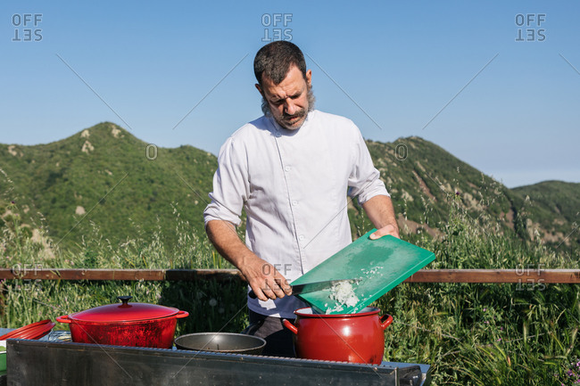 Serious bearded male cook in uniform adding cutting onion in soup while preparing different dishes in outdoor restaurant in countryside