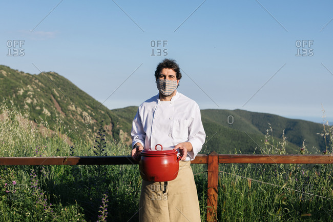 Anonymous male cook in apron medial mask standing against picturesque mountains in countryside with saucepan in hands
