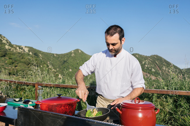 Crop concentrated male chef in tunic and apron preparing delicious dish in pan standing at table in outdoor kitchen against picturesque mountains