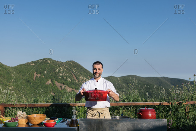 Professional cook in uniform standing with saucepan in the hands against mountainous terrain on sunny day