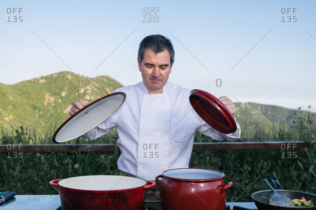 Male chef in uniform standing near saucepans in outdoor kitchen with mountains view while watching what you cook