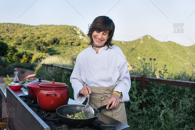 Positive female chef in apron and tunic preparing delicious dish in pan standing at stove in outdoor kitchen against magnificent landscape