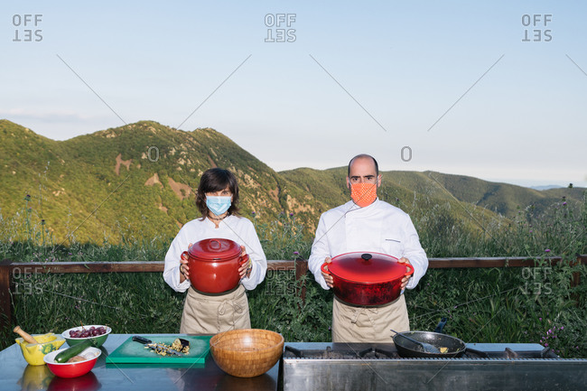 Anonymous professional cooks in uniforms and medical masks standing with saucepans in hands against mountainous terrain on sunny day