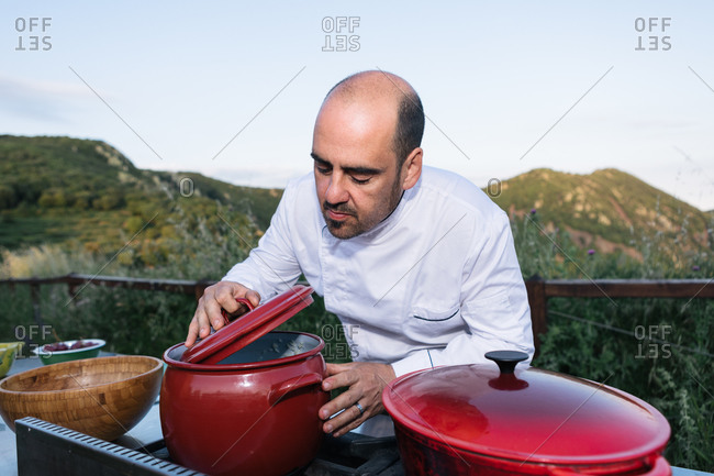Concentrated male chef in uniform smelling dish in saucepan while preparing dinner in countryside