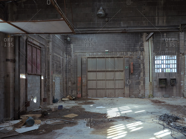 Weathered facility of abandoned industrial building of plant with rusty metal ceiling and shabby concrete floor