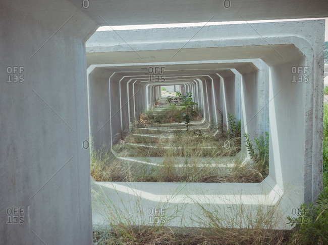 Perspective view of narrow passage with concrete walls and green grass during daytime