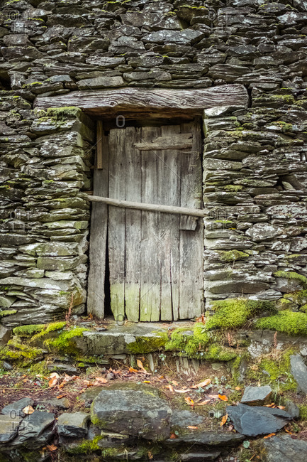 Wooden shed door with shabby surface closed with thick stick in historical countryside