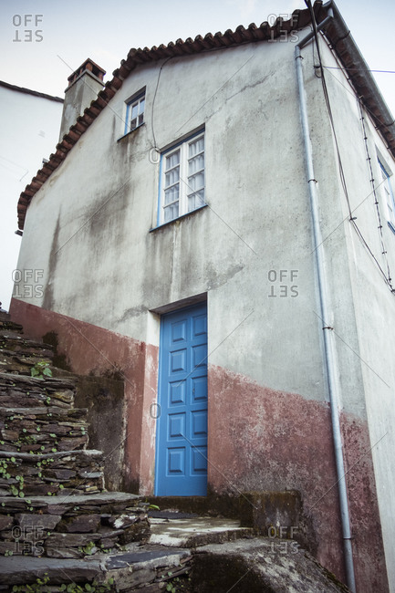 Facade of aged residential house with weathered cement walls and blue door under windows near old stone stairway under cloudy sky