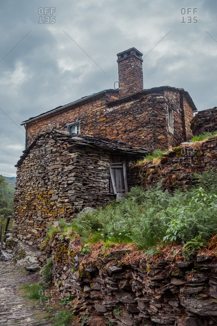 Exterior of old stone house with rough surface and chimney on top near green plants and pathway under cloudy sky