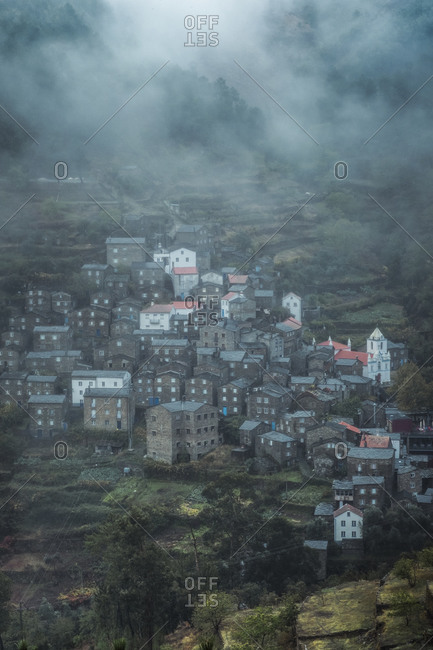 From above of scenery view of village with stone residential buildings surrounded by trees and mountains in foggy weather