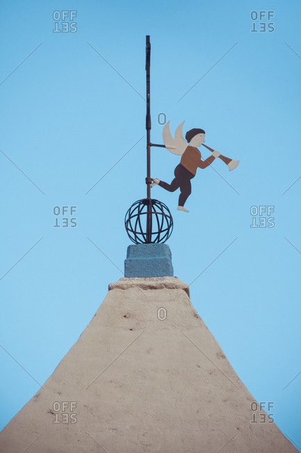 From below of weather vane in shape of little angle playing musical instrument on cross of temple dome under blue sky